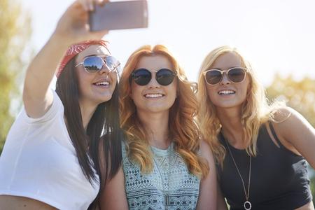 gafas de sol: Tres mejores amigos que toman un selfie aire libre Foto de archivo