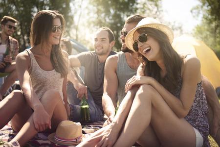 amigos hablando: Grupo de amigos hablando y riendo en la playa Foto de archivo