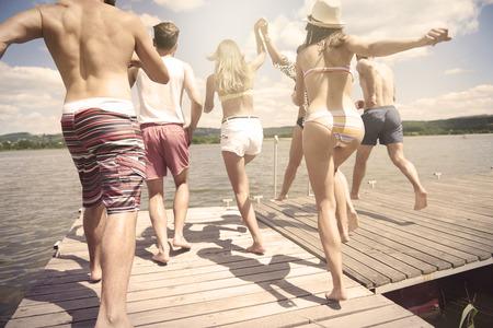 jumping: Las personas a punto de saltar en el agua Foto de archivo
