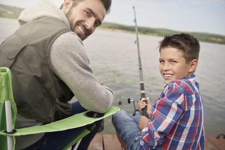 hombre pescando: Padre e hijo sentado en el muelle y la pesca