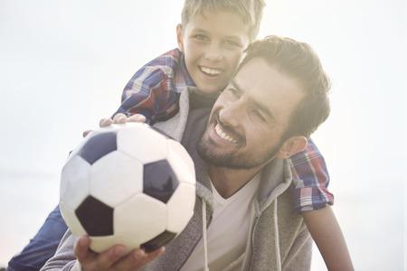 父の息子サッカーをプレイする方法を教えています。