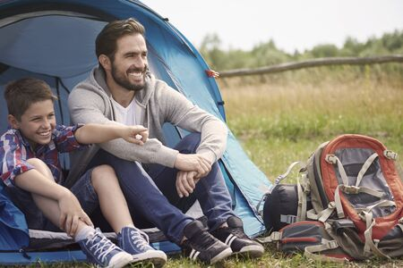 camping equipment: Father and son resting outside the tent