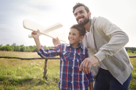 Père et fils tester un avion en papier