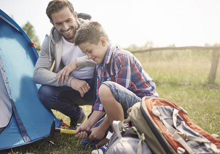 camping equipment: Father teaching son how to pitch a tent