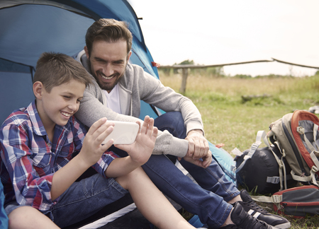 camping tent: Boy using his smartphone on the camping Stock Photo