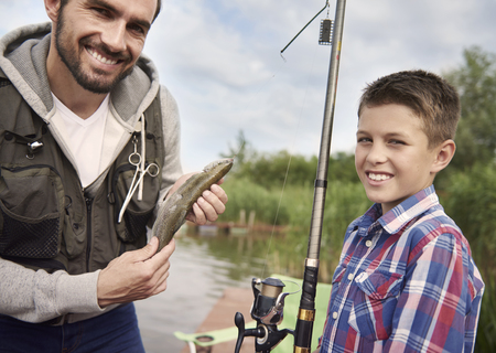 fishing pier: Father and son are very proud of their fish
