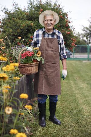 hombre con sombrero: Happy retiree holding basket full of flowers Foto de archivo