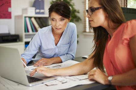 ayudando: Dos mujeres que consultan los datos en el ordenador Foto de archivo