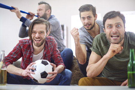 vuvuzela: Football fans watching match at home Stock Photo