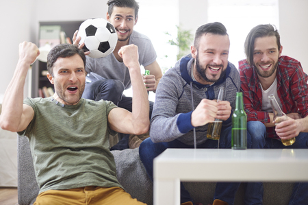 personas viendo television: Group of young men watching a match on TV Foto de archivo