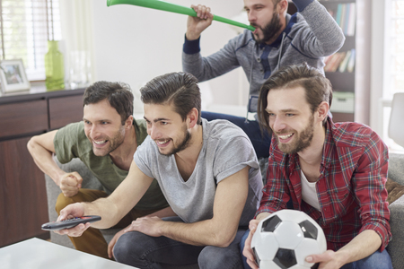 group of men: Make it louder because our team is winning Stock Photo