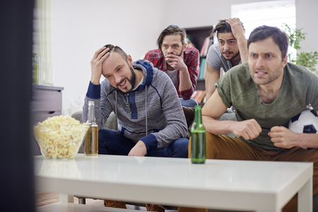 indoor soccer: Disappointed men watching soccer match