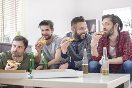 pizza: Amigos viendo la televisión y comiendo pizza