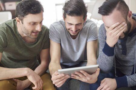 grupo de hombres: Amigos viendo fotos de sus viejos tiempos