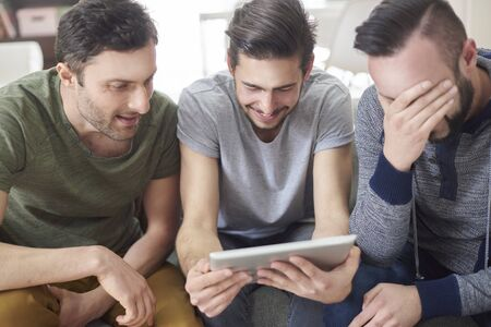 group of men: Friends browsing photos from their old times Stock Photo