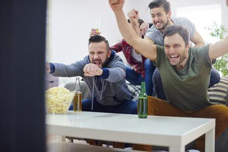 personas viendo television: Los hombres son orgullosos de su equipo que gan� el juego Foto de archivo