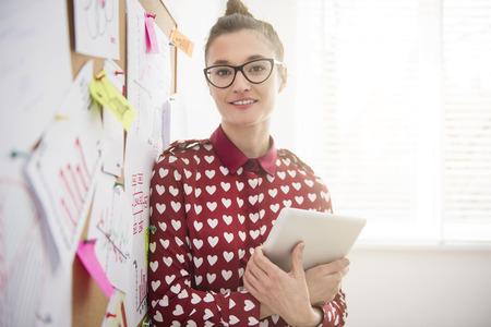 デジタル タブレットの彼女とポーズ物思いにふける実業家