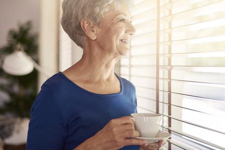 woman window: Senior woman drinking coffee next to the window Stock Photo