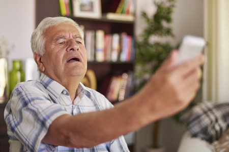 text space: Senior man having problem with his eye sight