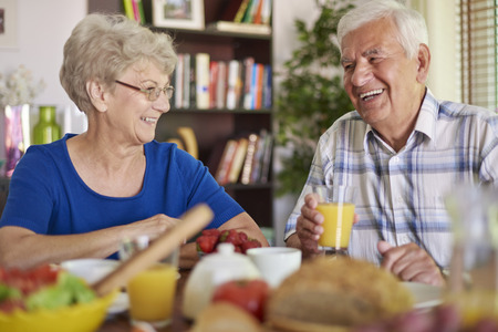 Cheerful grandparents eating breakfast together