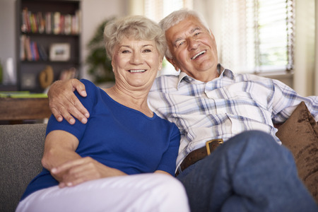 couple on couch: Happy mature marriage sitting on the sofa