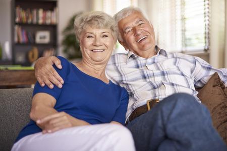 persona de la tercera edad: matrimonio maduro feliz sentado en el sofá Foto de archivo