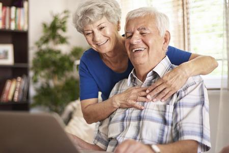 Happy grandparents using their digital laptop