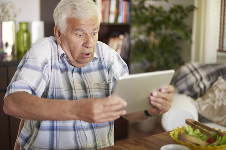Shocked senior man holding his tablet Stock Photo