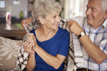 vitality: Husband giving warm blanket to his wife Stock Photo
