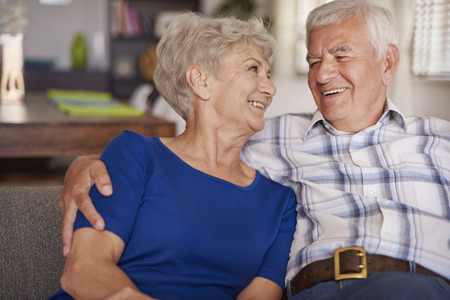 pareja abrazada: Pares mayores felices en el sof� te