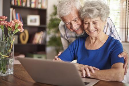pareja abrazada: La tecnología moderna no es un problema para ellos Foto de archivo