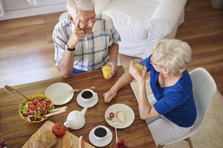 Elder couple eating breakfast together