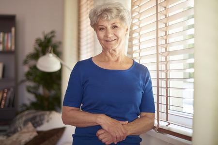 gente sentada: abuela alegre de pie junto a la ventana