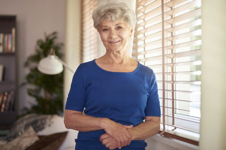 blind people: Cheerful grandmother standing next to the window