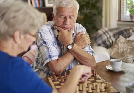 playing chess: Pensive face of senior man playing chess Stock Photo
