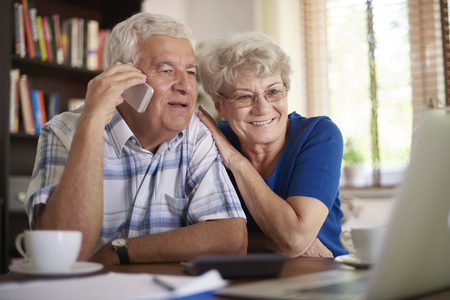 deal making: Smiling senior couple making  deal via telephone