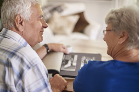 photo album book: Couple of elder couple reminiscing their past Stock Photo