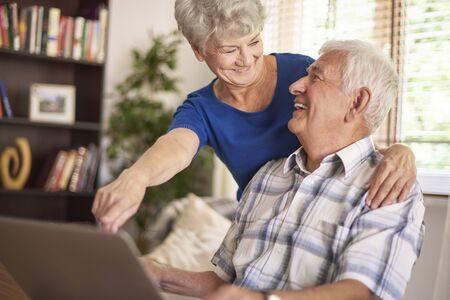 pareja en casa: Matrimonio anciano utilizando su computadora portátil junto