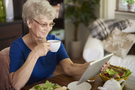 Cheerful senior woman eating breakfast and surfing the Internet photo