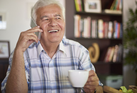 cup of coffee: Senior man talking on his mobile phone Stock Photo