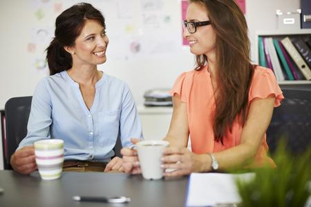 break from work: Little break and gossip with friend at work Stock Photo