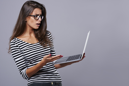 girl with laptop: Woman having problem with her wireless Internet Stock Photo