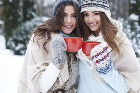 two girls hugging: Sip of hot tea to warm up