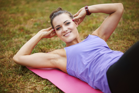 sit ups: Woman doing situps exercises in the city park