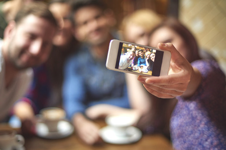 social gathering: Group of friends taking selfie in the cafe Stock Photo