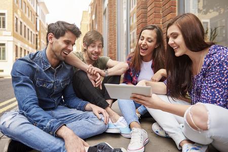 personas sentadas: La gente joven navegando por Internet