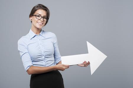 flecha direccion: Arrow sign held by a very attractive woman