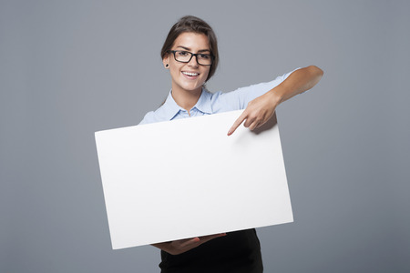 a placard: Beautiful businesswoman showing on empty whiteboard Stock Photo
