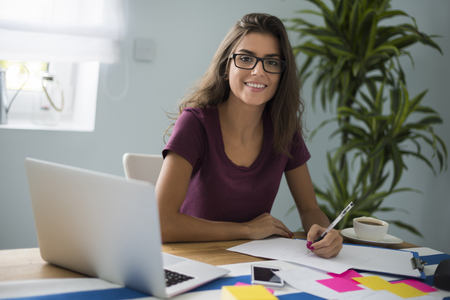 writing desk: Hardworking woman doesnt seem tired Stock Photo