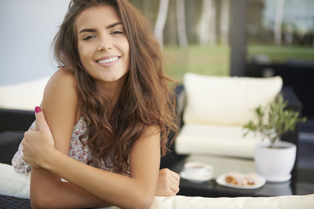 women sitting: Portrait of charming young woman on terrace Stock Photo